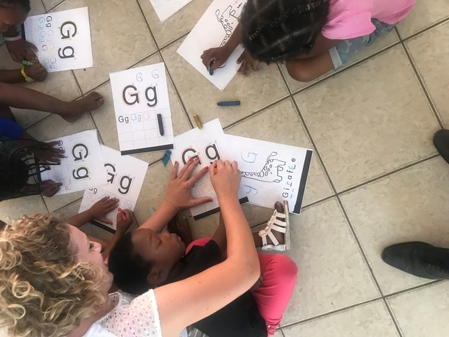 English students colouring withthe younger ones